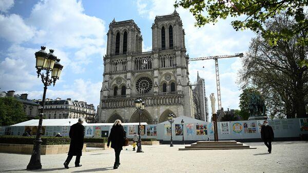 Люди гуляют перед собором Парижской Богоматери во время восстановительных работ