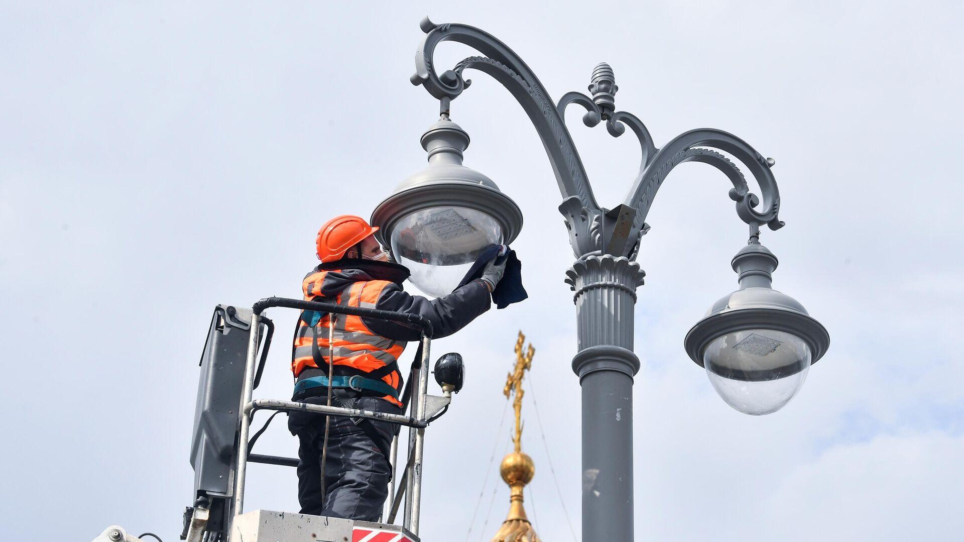 Сотрудник коммунальной службы протирает плафон фонаря наружного освещения на Пречистенской набережной в Москве - РИА Новости, 1920, 22.07.2021