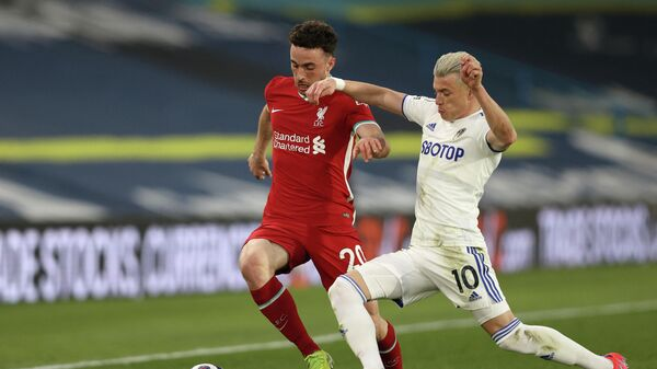 Leeds United's Macedonian midfielder Ezgjan Alioski (R) challenges Liverpool's Portuguese striker Diogo Jota (L) during the English Premier League football match between Leeds United and Liverpool at Elland Road in Leeds, northern England on April 19, 2021. (Photo by Clive Brunskill / POOL / AFP) / RESTRICTED TO EDITORIAL USE. No use with unauthorized audio, video, data, fixture lists, club/league logos or 'live' services. Online in-match use limited to 120 images. An additional 40 images may be used in extra time. No video emulation. Social media in-match use limited to 120 images. An additional 40 images may be used in extra time. No use in betting publications, games or single club/league/player publications. /