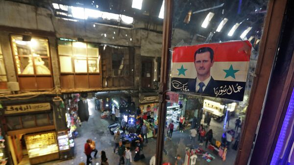 Плакат с изображением президента Сирии Башара Асада на рынке в Дамаске