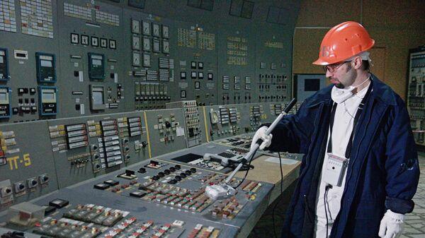 Рабочий измеряет уровень радиации в щитовой третьего энергоблока Чернобыльской АЭС