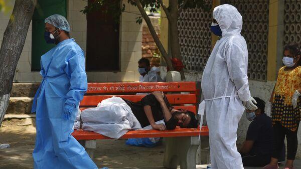 Медицинские работники во время массовой кремации жертв пандемии в Дели