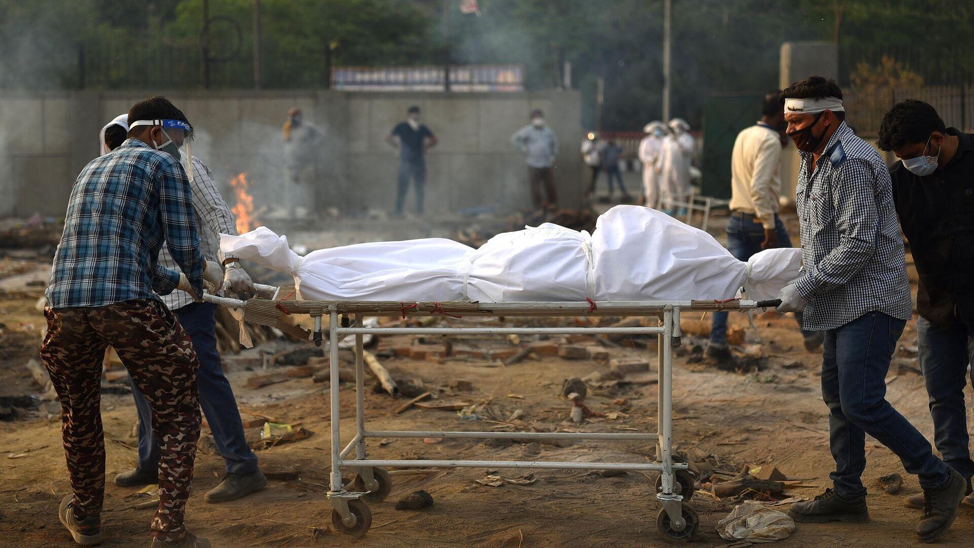 Подготовка тела погибшего к кремации жертв пандемии в Дели - РИА Новости, 1920, 06.05.2021