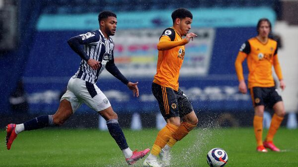 West Bromwich Albion's English defender Darnell Furlong (L) closes in on Wolverhampton Wanderers' English midfielder Morgan Gibbs-White during the English Premier League football match between West Bromwich Albion and Wolverhampton Wanderers at The Hawthorns in West Bromwich, central England on May 3, 2021. (Photo by Jason CAIRNDUFF / POOL / AFP) / RESTRICTED TO EDITORIAL USE. No use with unauthorized audio, video, data, fixture lists, club/league logos or 'live' services. Online in-match use limited to 120 images. An additional 40 images may be used in extra time. No video emulation. Social media in-match use limited to 120 images. An additional 40 images may be used in extra time. No use in betting publications, games or single club/league/player publications. /