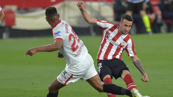 Athletic Bilbao's Spanish forward Alex Berenguer (R) fights for the ball with Sevilla's Brazilian midfielder Fernando during the Spanish League football match between Sevilla and Athletic Bilbao at the Ramon Sanchez Pizjuan stadium in Seville on May 3, 2021. (Photo by CRISTINA QUICLER / AFP)