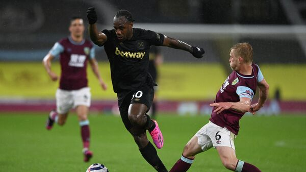 West Ham United's English midfielder Michail Antonio (C) avoids the tackle of Burnley's English defender Ben Mee during the English Premier League football match between Burnley and West Ham United at Turf Moor in Burnley, north west England, on May 3, 2021. (Photo by GARETH COPLEY / POOL / AFP) / RESTRICTED TO EDITORIAL USE. No use with unauthorized audio, video, data, fixture lists, club/league logos or 'live' services. Online in-match use limited to 120 images. An additional 40 images may be used in extra time. No video emulation. Social media in-match use limited to 120 images. An additional 40 images may be used in extra time. No use in betting publications, games or single club/league/player publications. /