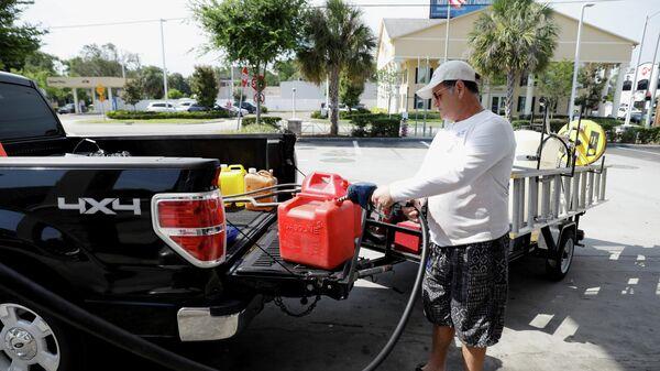 Мужчина наполняет канистры топливом после кибератаки на трубопровод компании Colonial Pipeline в Тампе, Флорида, США