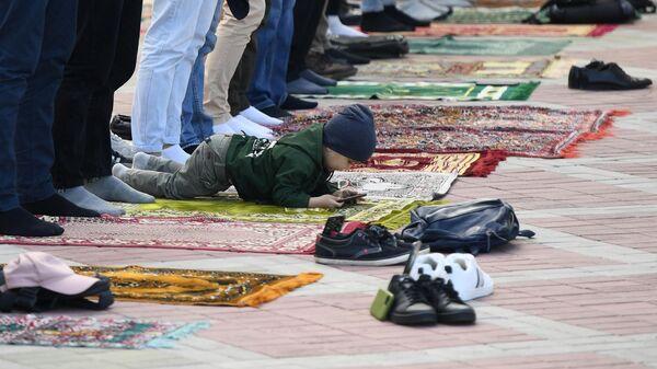Мальчик во время праздничной молитвы в честь Ураза-байрама возле мечети Кул Шариф в Казани