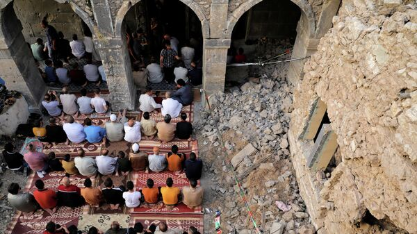 Люди во время молитвы Ид аль-Фитр, посвященной окончанию священного месяца поста Рамадан, в самой старой мечети Аль-Масфи, которая была повреждена во время войны с боевиками Исламского государства в Мосуле, Ирак