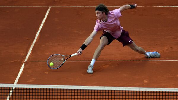 Russia's Andrey Rublev returns the ball to US John Isner during their 2021 ATP Tour Madrid Open tennis tournament singles match at the Caja Magica in Madrid on May 6, 2021. (Photo by OSCAR DEL POZO / AFP)