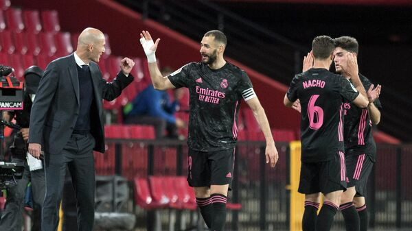 Real Madrid's French forward Karim Benzema celebrates with Real Madrid's French coach Zinedine Zidane after scoring a goal during the Spanish league football match Granada FC against Real Madrid CF at the Nuevo Los Carmenes stadium in Granada on May 13, 2021. (Photo by JORGE GUERRERO / AFP)