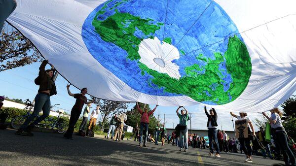Люди держат плакат с изображением планеты Земля в Сиэтле