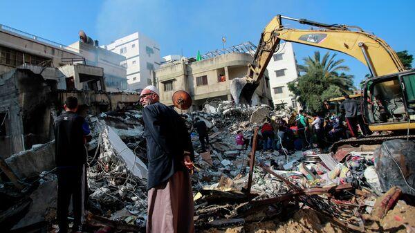 Спасатели разбирают обломки, разрушенного в результате бомбардировки здания, в секторе Газа