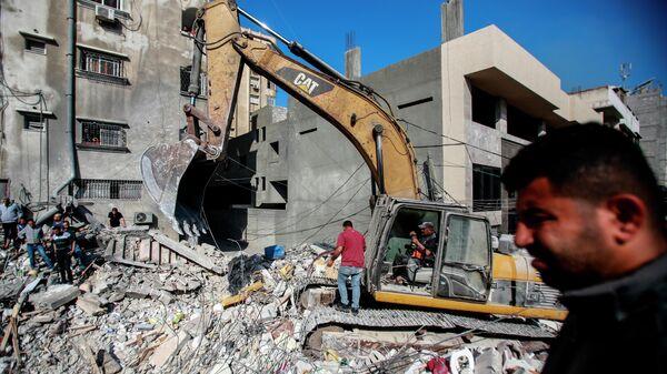 Спасатели разбирают завалы разрушенного в результате бомбардировки здания в секторе Газа