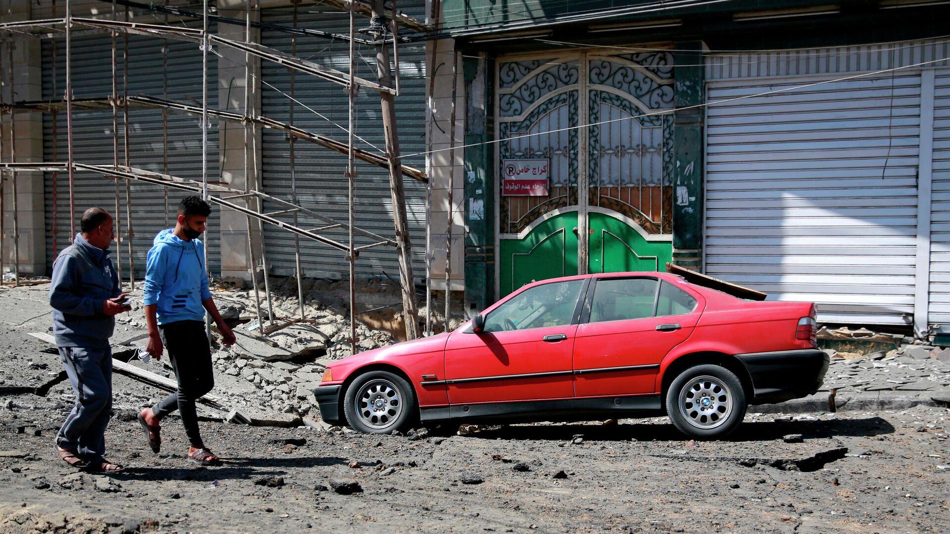 Молодые люди на улице в секторе Газа, пострадавшей в результате обстрела - РИА Новости, 1920, 17.05.2021