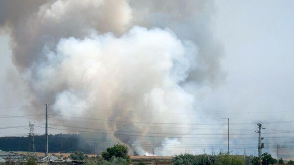 Пожар в поле, вызванный попаданием ракеты,  возле кибуца Гварам на юге Израиля