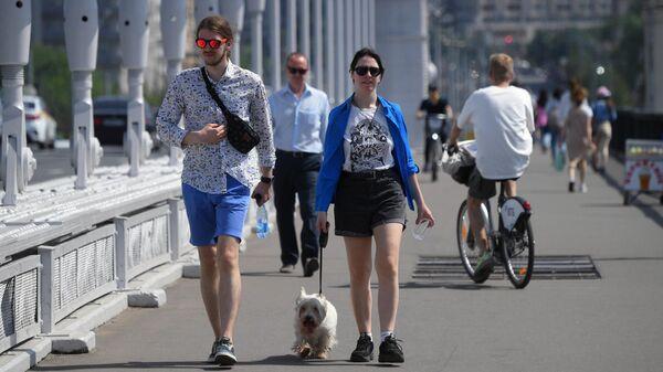 Молодые люди идут по Крымском мосту в Москве