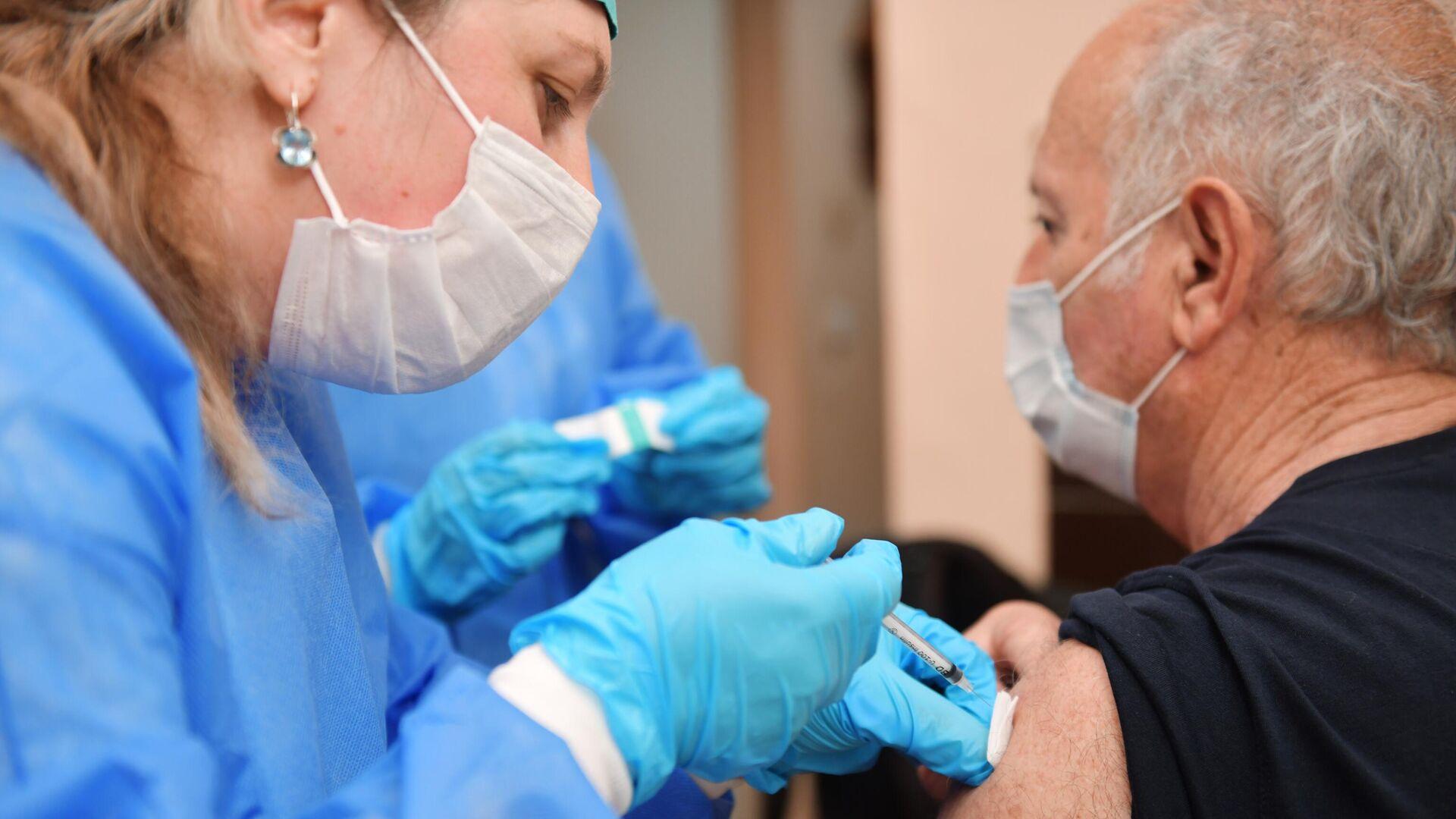 Медик прививает мужчину от коронавирусной инфекции COVID-19 российским препаратом Sputnik V в больнице в Сухуме - РИА Новости, 1920, 17.06.2021
