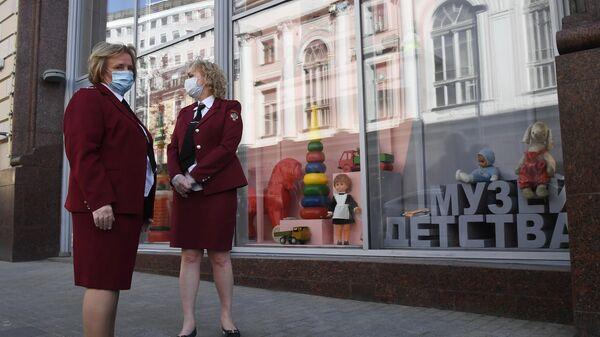 Сотрудники Роспотребнадзора у здания Центрального детского магазина в Москве, опечатанного за нарушение профилактических мер