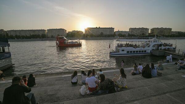 Отдыхающие на набережной в Парке Горького в Москве в жаркую погоду