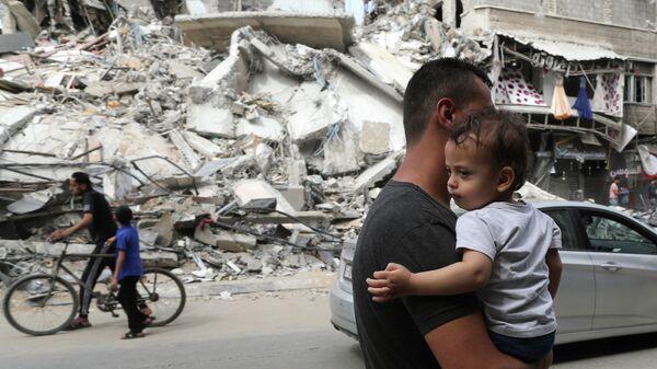 Палестинец с ребенком проходит мимо разрушенных в результате бомбардировки зданий в секторе Газа, после объявления о прекращении огня между Израилем и ХАМАС