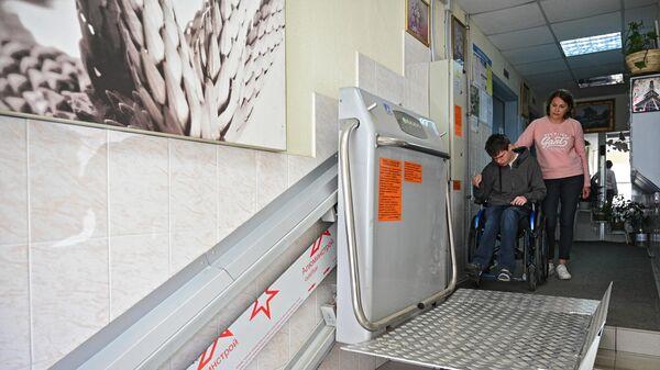 Подросток в инвалидной коляске у подъемной платформы для инвалидов в подъезде жилого дома