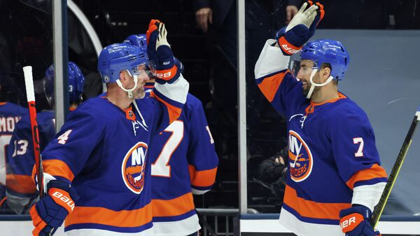 UNIONDALE, NEW YORK - MAY 22: Andy Greene #4 and Jordan Eberle #7 of the New York Islanders celebrate a 4-1 win over the Pittsburgh Penguins in Game Four of the First Round of the 2021 Stanley Cup Playoffs at the Nassau Coliseum on May 22, 2021 in Uniondale, New York.   Bruce Bennett/Getty Images/AFP (Photo by BRUCE BENNETT / GETTY IMAGES NORTH AMERICA / Getty Images via AFP)