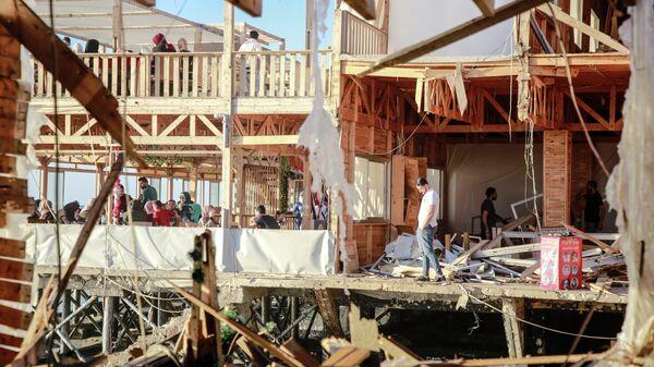 Люди на территории разрушенного дома в секторе Газа