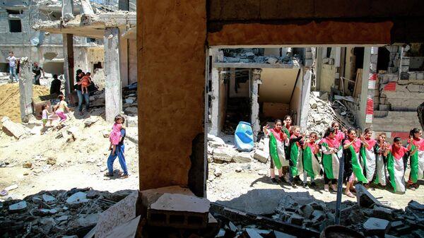 Дети у дома, разрушенного в результате бомбардировки на северо-востоке сектора Газа в городе Бейт-Ханун