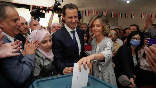 Асма Асад опускает бюллетень в урну во время выборов президента Сирии