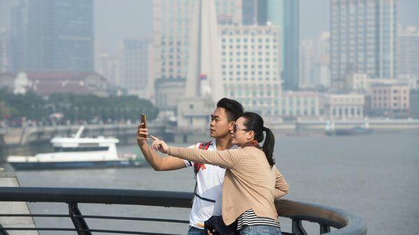 Молодые люди делают селфи на набережной в Китае