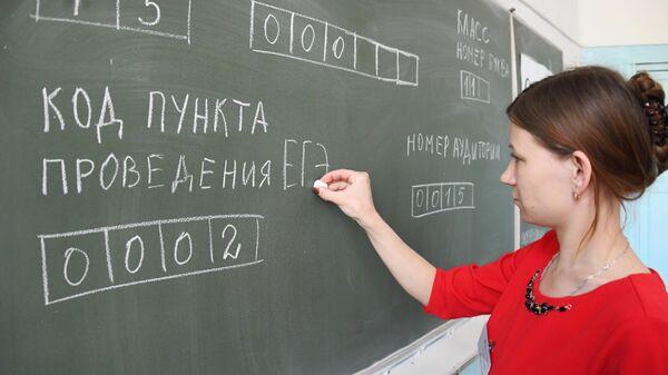 Учитель пишет на доске образец заполнения экзаменационного листа перед началом ЕГЭ по информатике и ИКТ