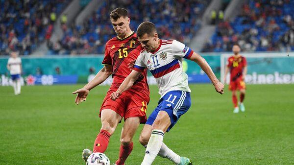 Игрок сборной Бельгии Тома Менье 9слева) и игрок сборной России Роман Зобнин в матче 1-го тура группового этапа чемпионата Европы по футболу 2020 между сборными Бельгии и России.