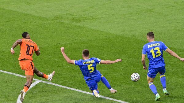 Форвард сборной Нидерландов Мемфис Депай (слева) наносит удар по воротам сборной Украины