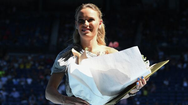 Denmark's Caroline Wozniacki holds a bouquet of flowers after a special ceremony following the women's singles semi-final match between Australia's Ashleigh Barty and Sofia Kenin of the US on day eleven of the Australian Open tennis tournament in Melbourne on January 30, 2020. (Photo by Manan VATSYAYANA / AFP) / IMAGE RESTRICTED TO EDITORIAL USE - STRICTLY NO COMMERCIAL USE