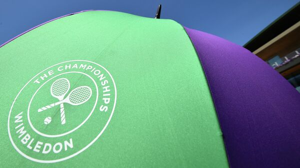 An unmbrella with the Wimbledon Championships tennis tournament's logo is seen at The All England Tennis Club in Wimbledon, southwest London, on July 4, 2019, on the fourth day of the 2019 Wimbledon Championships tennis tournament. (Photo by Glyn KIRK / AFP) / RESTRICTED TO EDITORIAL USE