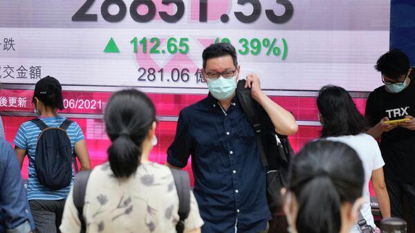 Люди в защитных масках проходят мимо табло с котировками ценных бумаг в Гонконге