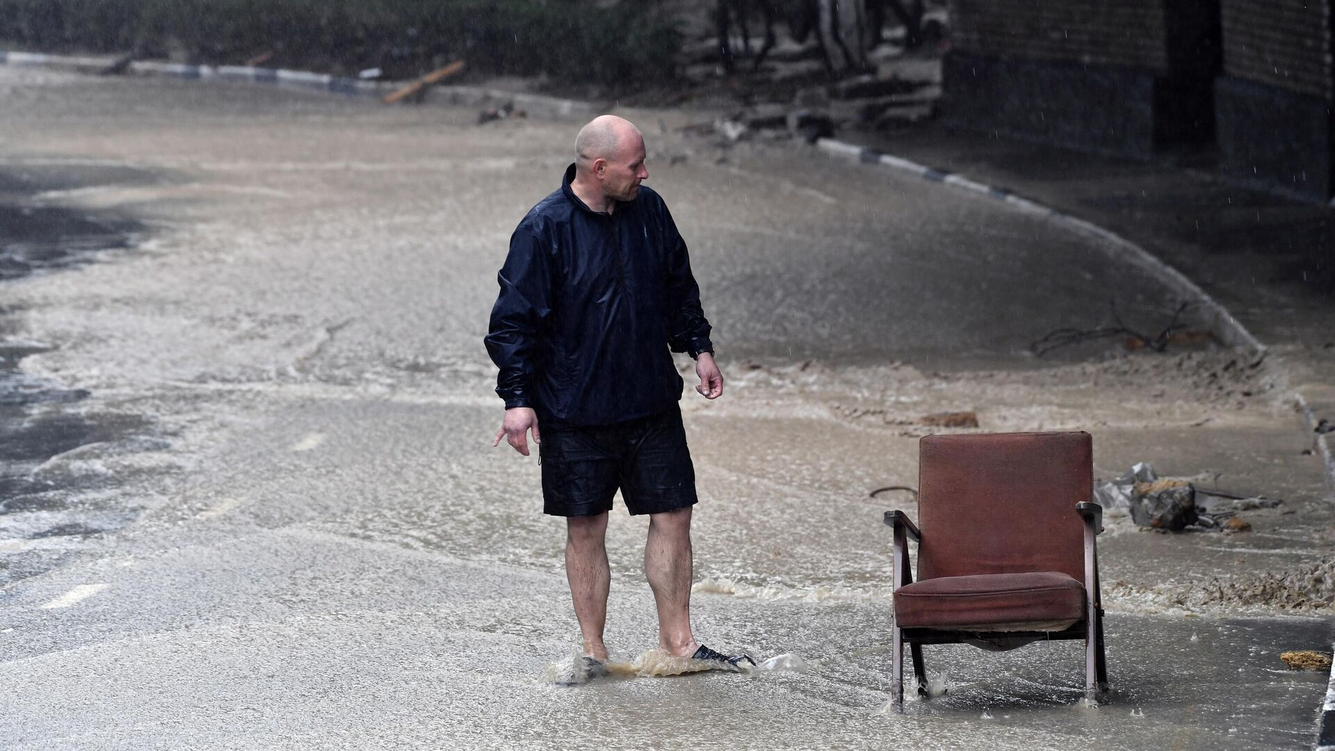 Мужчина на одной из улиц Ялты. В Крыму прошли сильные дожди, вызвавшие подтопления - РИА Новости, 1920, 19.06.2021