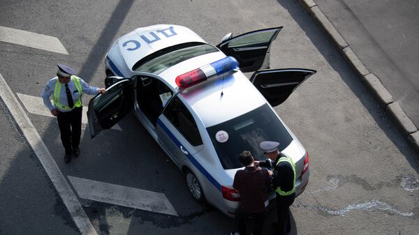 Сотрудник ДПС Государственной инспекции безопасности дорожного движения МВД РФ выписывает штраф нарушителю правил дорожного движения