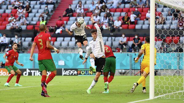 Полузащитник сборной Германии Робин Госенс забивает мяч в ворота португальцев