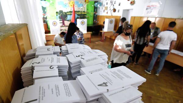 Люди на одном из избирательных участков во время досрочных парламентских выборов в Армении