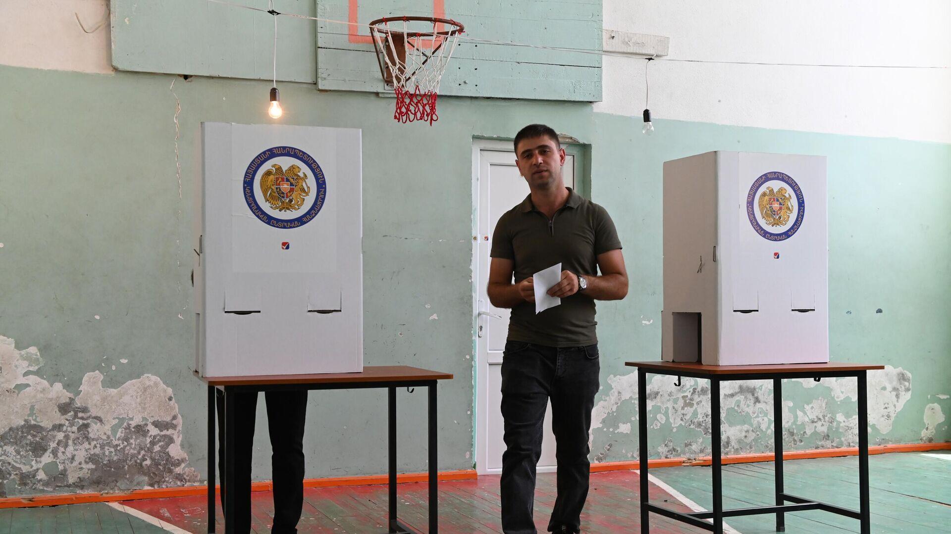 Мужчина голосует на одном из избирательных участков в Ереване во время досрочных парламентских выборов в Армении - РИА Новости, 1920, 27.06.2021