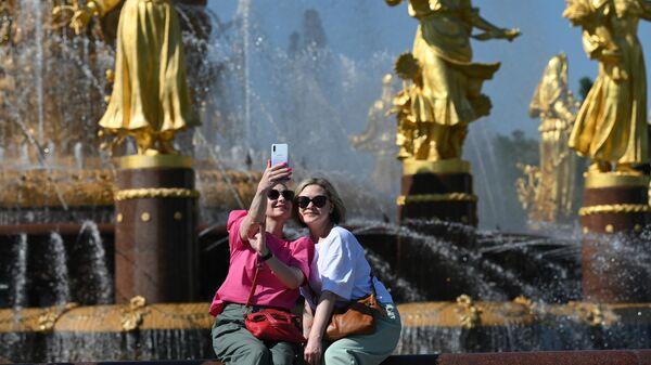 Девушки отдыхают в жаркую погоду у фонтана Дружба народов на ВДНХ