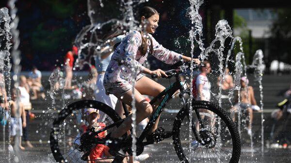 Девушка на велосипеде в Парке искусств Музеон в Москве в жаркую погоду
