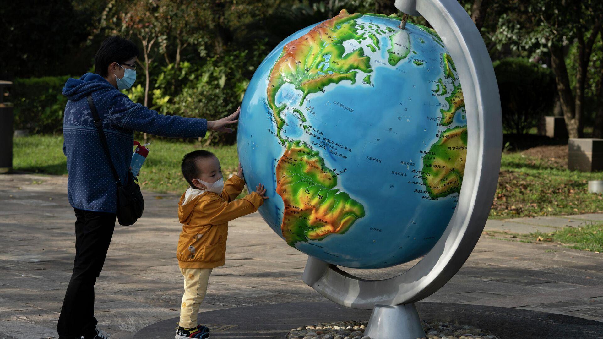 Женщина с ребенком у глобуса в парке в Ухани, Китай - РИА Новости, 1920, 23.06.2021