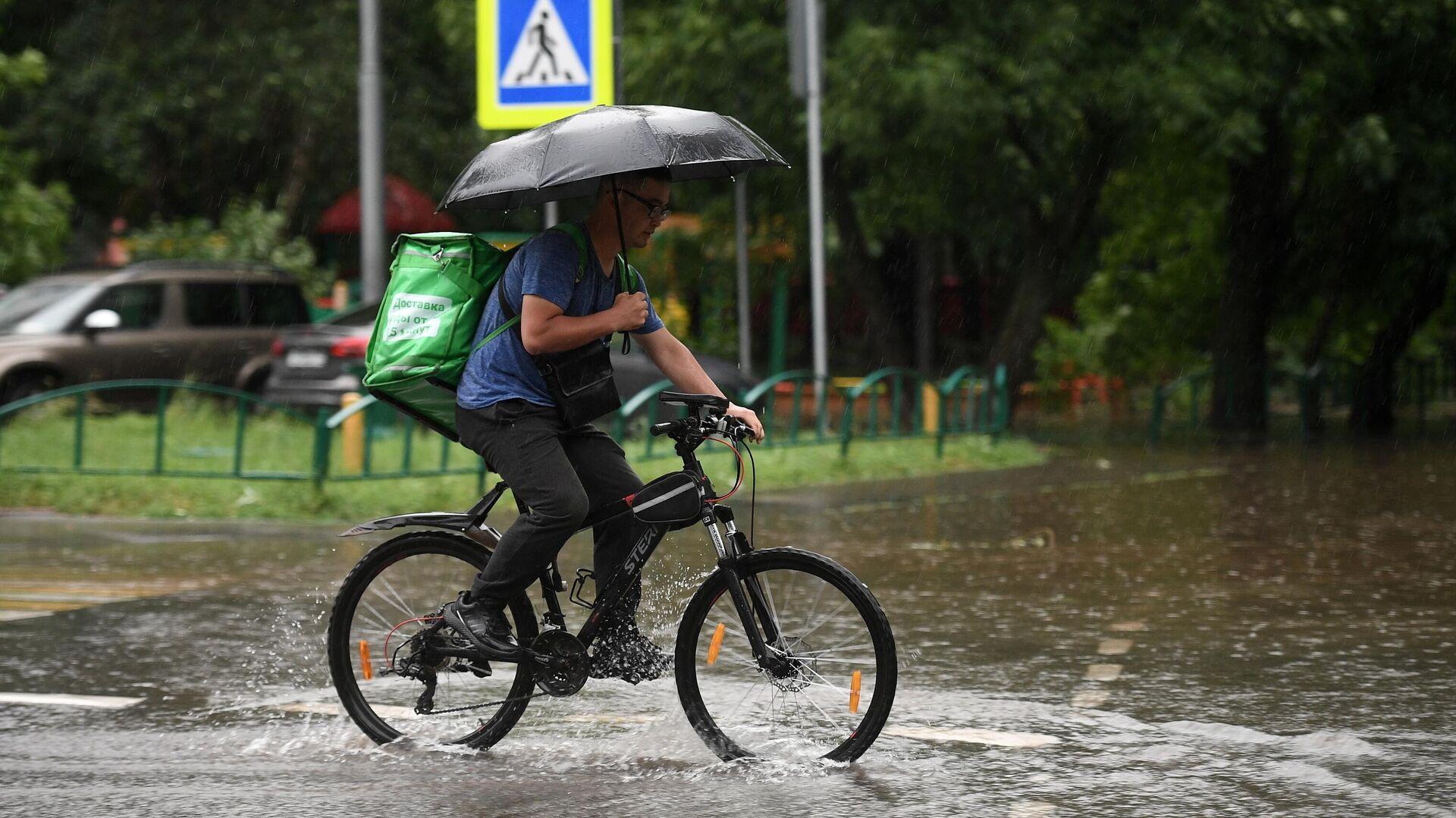 Мужчина едет на велосипеде по одной из улиц в Москве во время дождя - РИА Новости, 1920, 01.08.2021