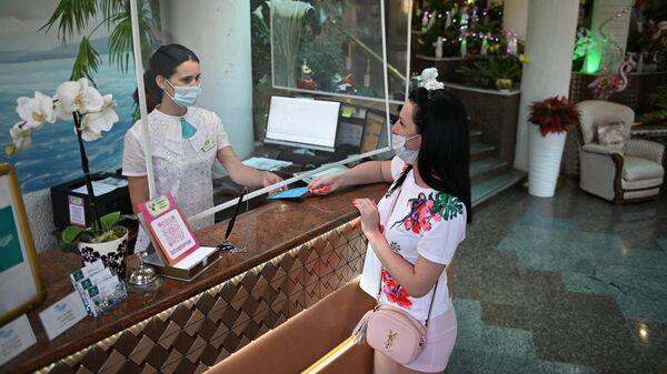 Сотрудница санатория проверяет сертификат о вакцинации от CoVID-19 у гостьи перед заселением в номер