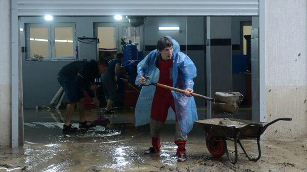 Мужчина устраняет последствия подтопления на станции технического обслуживания автомобилей в Хостинском районе Сочи