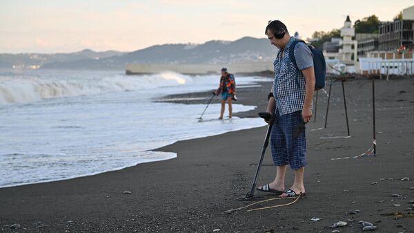 Люди с металлоискателями на пляже Ривьера в Сочи после подтопления