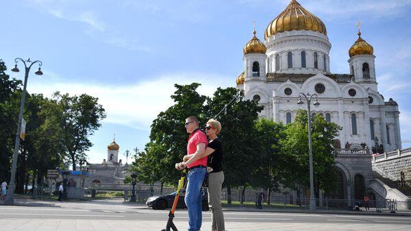 Люди катаются на самокате на Пречистенской набережной в Москве